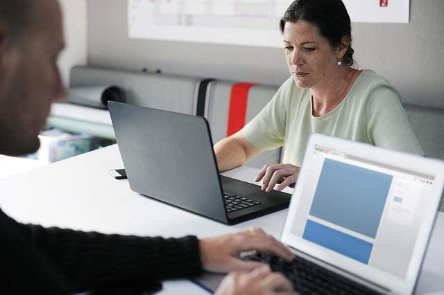 Slecht functioneren medewerker - 2 mensen tegenover elkaar achter laptops