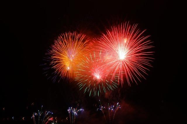 foto van vuurwerk in rood geel en groen tegen een donkere lucht