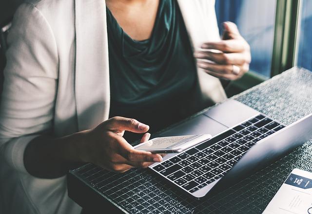 werkdruk verminderen - persoon achter laptop met smartphone