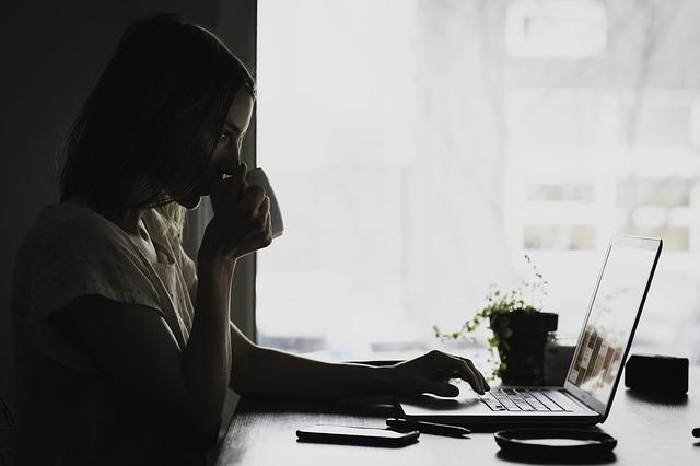 Minder overwerken - vrouw in donker achter laptop drinkt koffie
