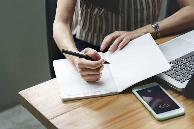 Blended Coaching - iemand die in een schrift schrijft