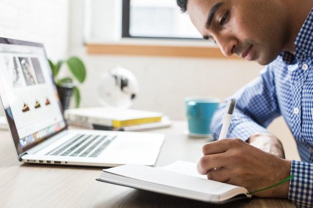 persoon schrijft voor laptop op blog over voordelen online coaching