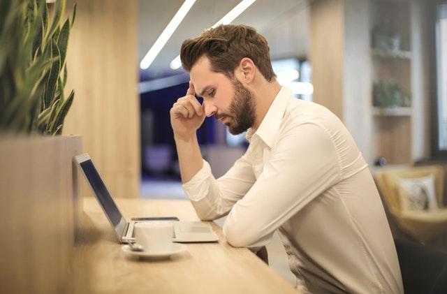 persoon zittend voor laptop op pagina over werkstress