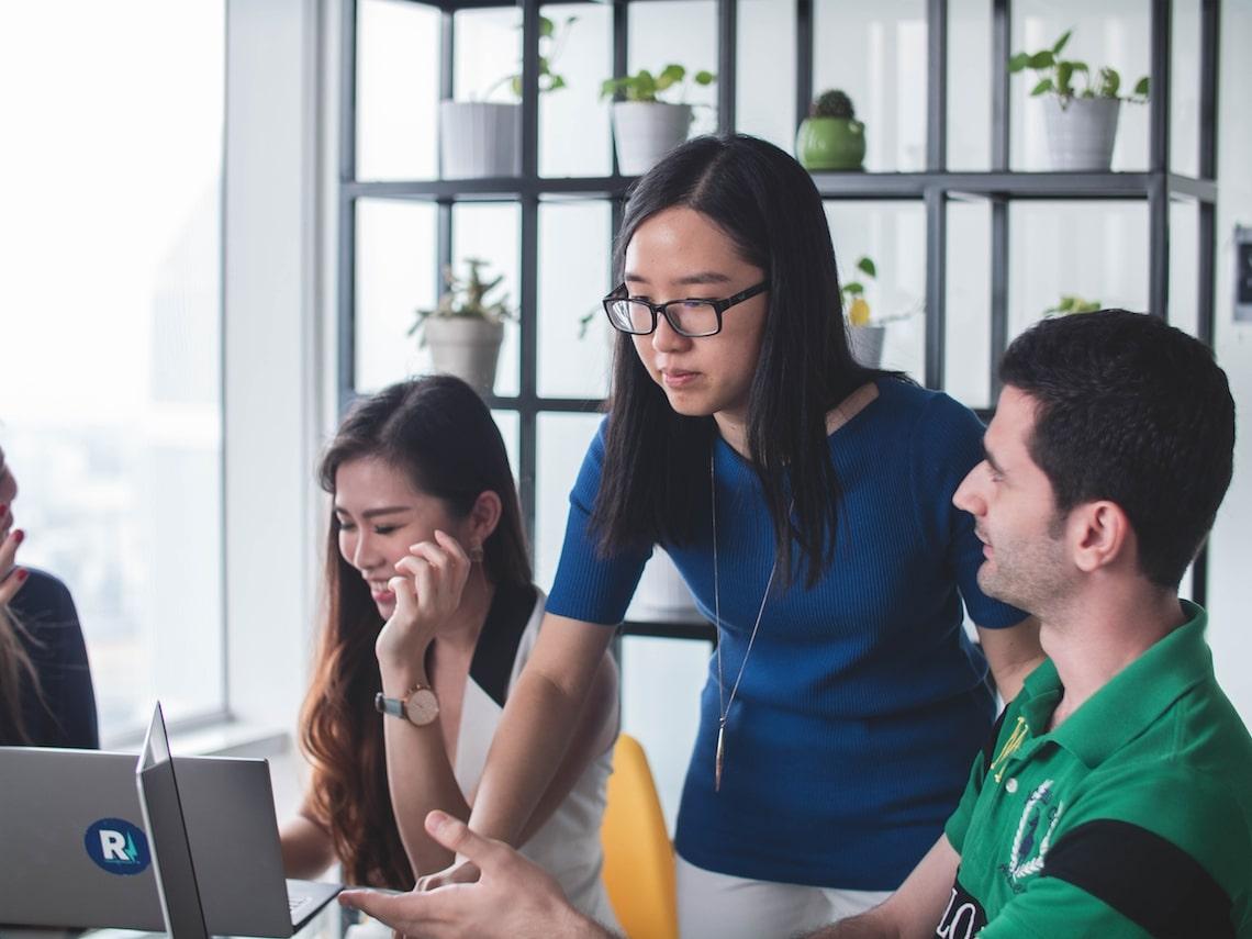 paar mensen bij laptop die overleggen in blog over valkuilen coachend leidinggeven