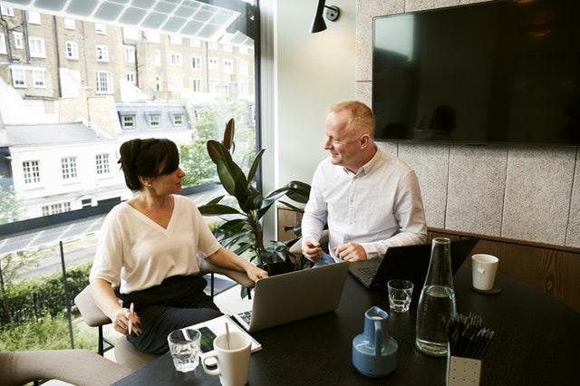 Een man en vrouw praten met elkaar in een kantoor. Ze zitten beiden achter een laptop en kijken elkaar aan.