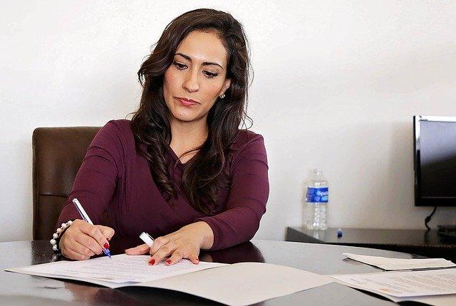 Een vrouw met lang, donker haar, zit achter een bureau. Ze houd in haar ene hand een pen vast en schrijft daarmee op een document. De andere hand ligt op het document en houdt de dop vast. Op de achtergrond zien we een waterflesje met de dop eraf en een deel van een beeldscherm.