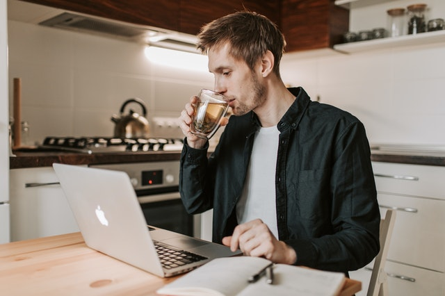 man voor laptop in keuken in blog over online leidinggeven